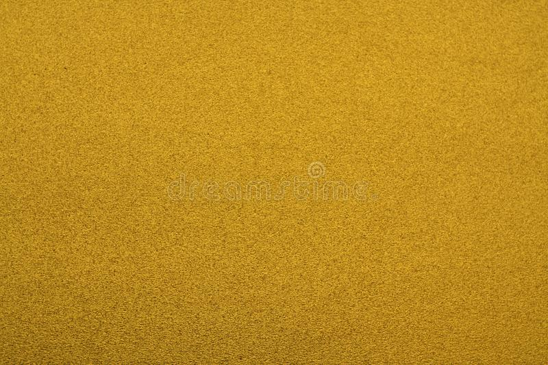 Plastic glittering texture. Abstract background and texture for design gold yellow hot color backdrop bright doormat pattern light shiny surface bokeh royalty free stock photo