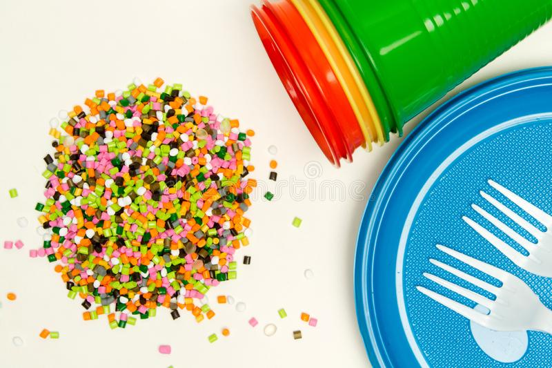 Plastic granules and disposable tableware made of polyethylene, polypropylene against the background of a polymeric material. BPA. FREE, granulate, hdpe, heap royalty free stock photo