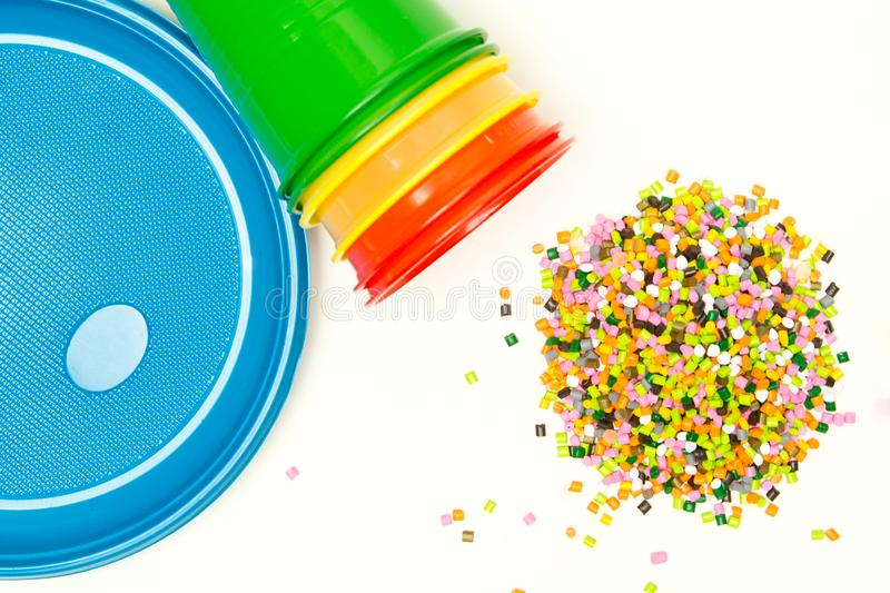Plastic granules and disposable tableware made of polyethylene, polypropylene against the background of a polymeric material. BPA. FREE, granulate, hdpe, heap stock images