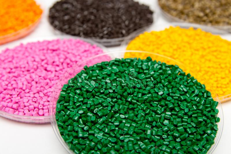 The plastic granules. Dye for polypropylene, polystyrene granules into a measuring container.  stock photos