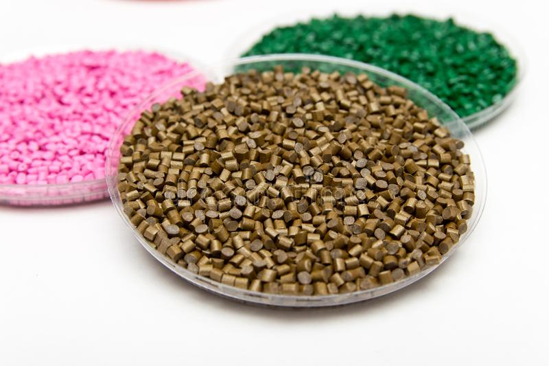 The plastic granules. Dye for polypropylene, polystyrene granules into a measuring container.  stock photography