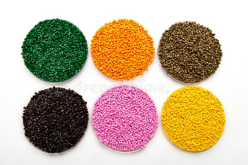 The plastic granules. Dye for polypropylene, polystyrene granules into a measuring container. The plastic granules. Dye for polypropylene, polystyrene granules stock photo