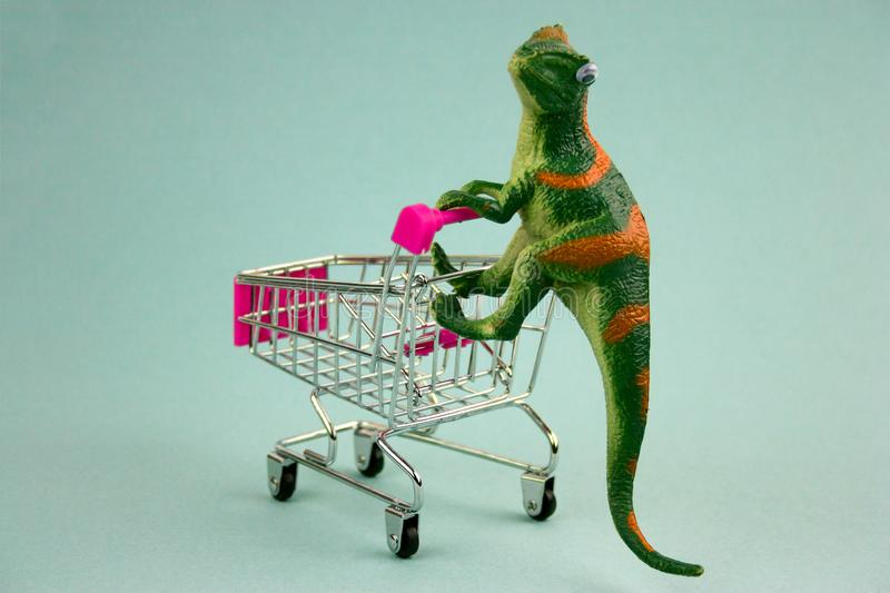 Plastic green dinosaur with shopping cart stock image