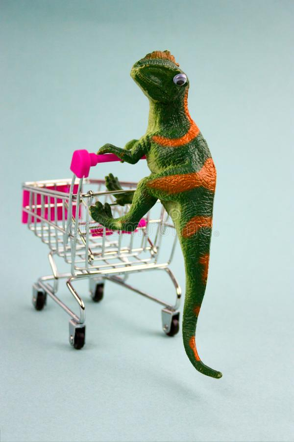 Green dinosaur with shopping cart stock photography