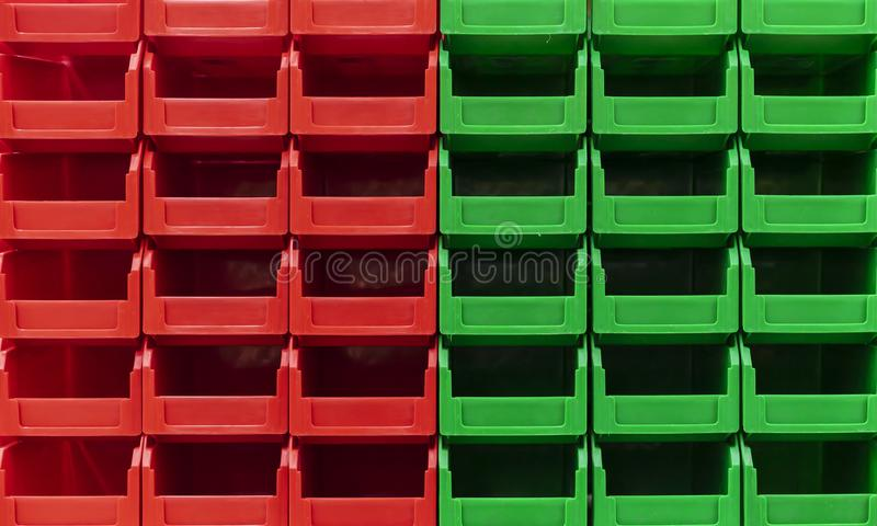 Plastic green and red containers are stacked in several rows stock photos
