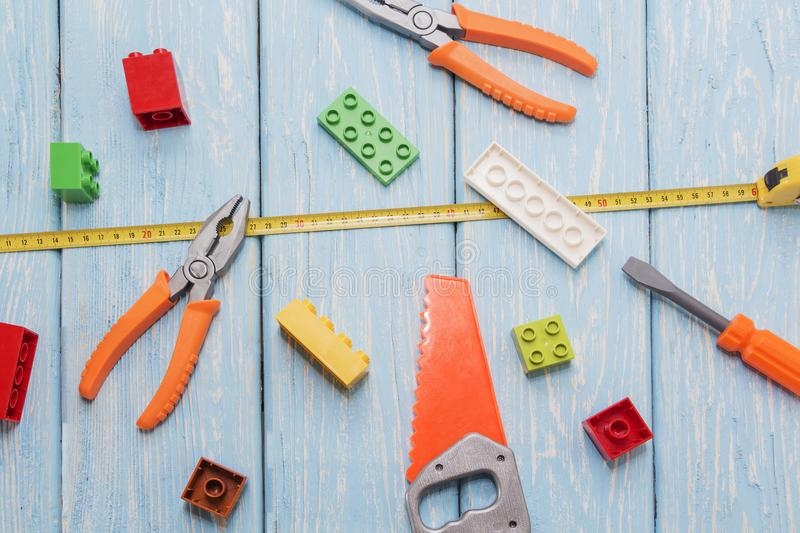 Plastic hammer, saw, pliers, toys. Plastic hammer, saw, pliers, toys On light wooden blue background stock image
