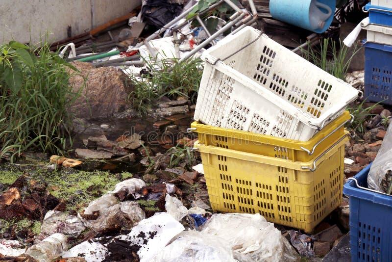 Plastic het Kratdoos van de fruitmand en Stapel van Afval plastic zakken, Plastic zak in de rotte rivier van het waterafval, Huis royalty-vrije stock afbeeldingen