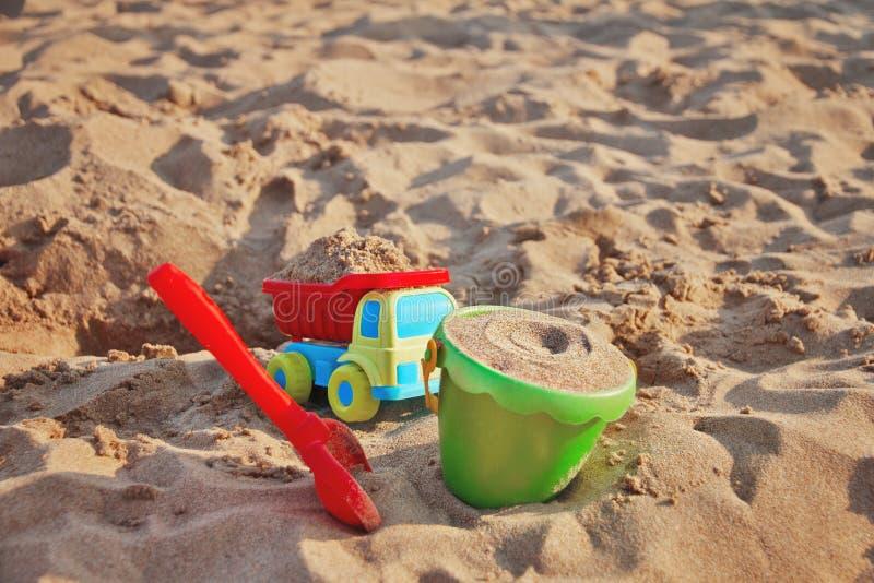 Plastic het speelgoed groene emmer van kinderen, gele ladingsvrachtwagen, rode schop met geel zand op het strand door overzees royalty-vrije stock fotografie