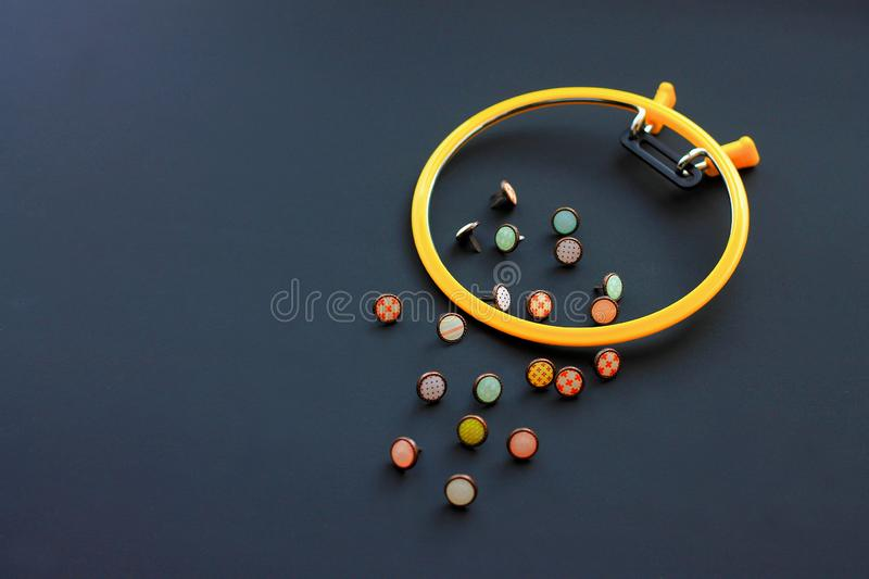 Plastic hoop for embroidery and buttons for clothes on a black background royalty free stock photos