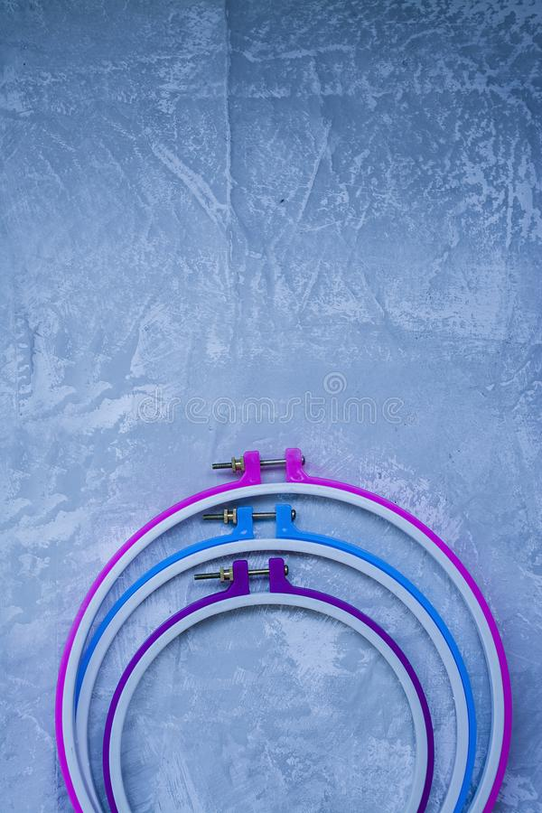 Plastic hoop on a light background under the concrete. Three hoops pink, blue, purple. View from above. Space under the text.  royalty free stock photography