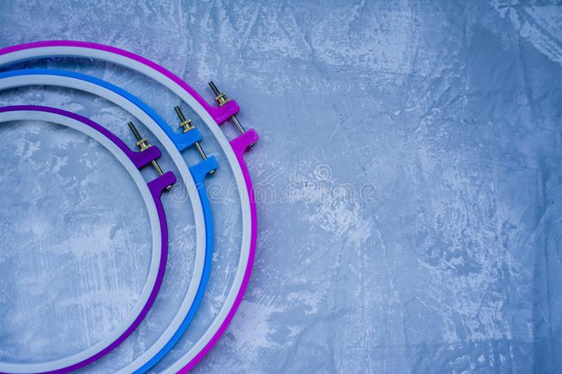 Plastic hoop on a light background under the concrete. Three hoops pink, blue, purple. View from above. Space under the text.  royalty free stock images