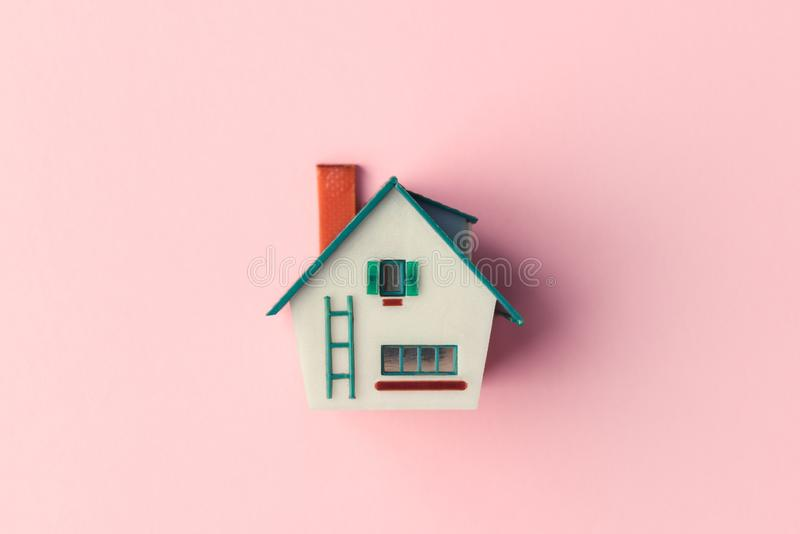 Plastic house model. On pink background. Real estate concept stock image