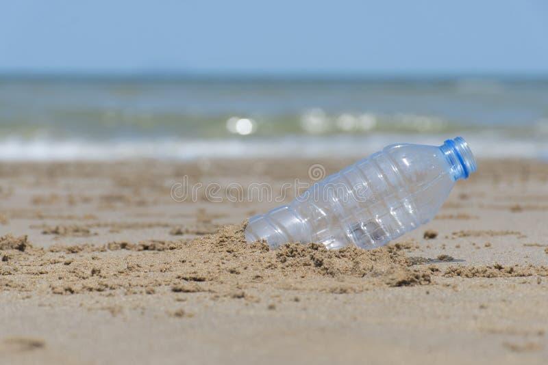Plastic huisvuil dat op het strand als slechte milieu en verontreiniging wordt gelaten vallen royalty-vrije stock afbeelding