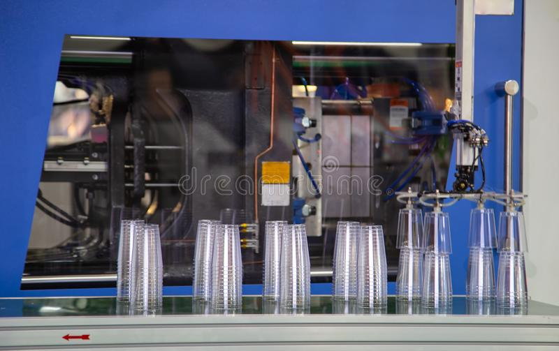 Plastic injection molding press machine. Disposable plastic cup product from plastic injection molding press machine royalty free stock photos