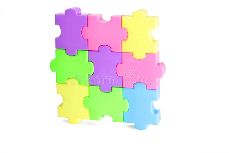 Plastic jigsaw puzzles. Colorful plastic jigsaw puzzle blocks on white background stock images