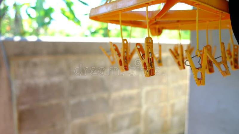 Plastic kleerhanger, close-up oranje hanger, muur als achtergrond stock afbeeldingen
