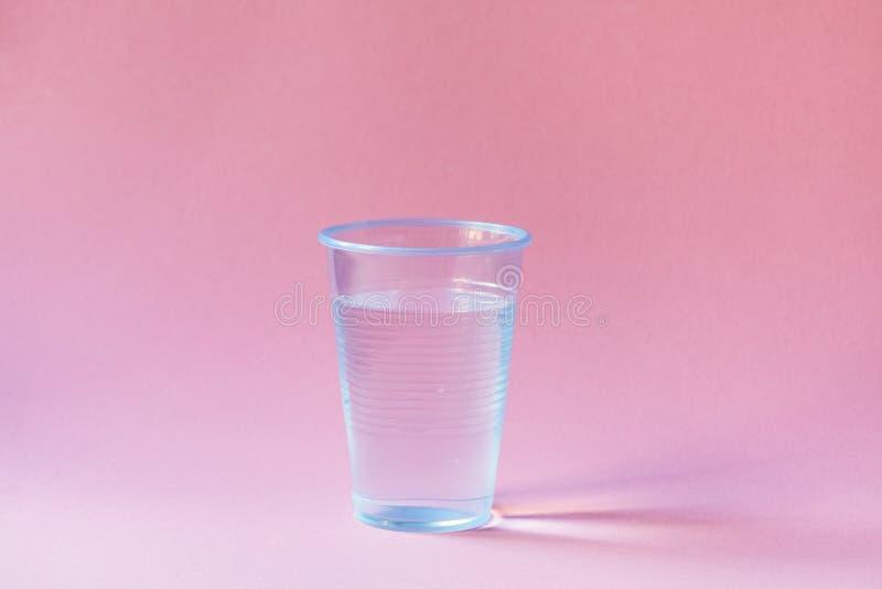 Plastic kop van mineraalwater op roze royalty-vrije stock fotografie