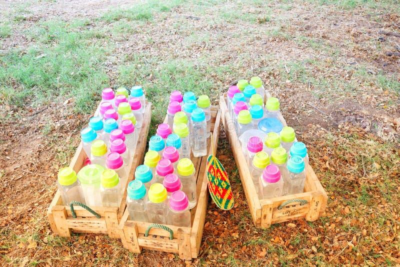 Plastic kratten met kleurrijke plastic watertanks, rood, geel roze, groen, blauw, stock afbeelding