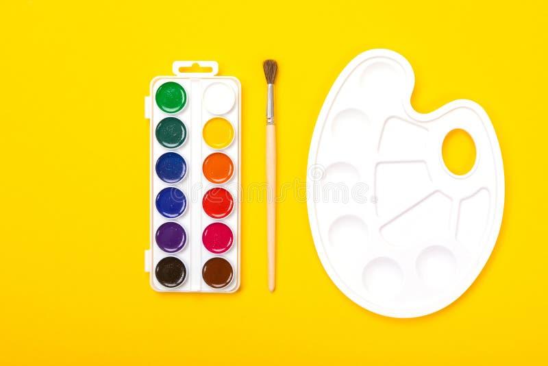 Plastic kunstpalet met waterverfverven en borstel op oranje achtergrond royalty-vrije stock fotografie