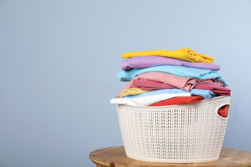 Plastic laundry basket with clean clothes on stool against color background. Space for text stock photos