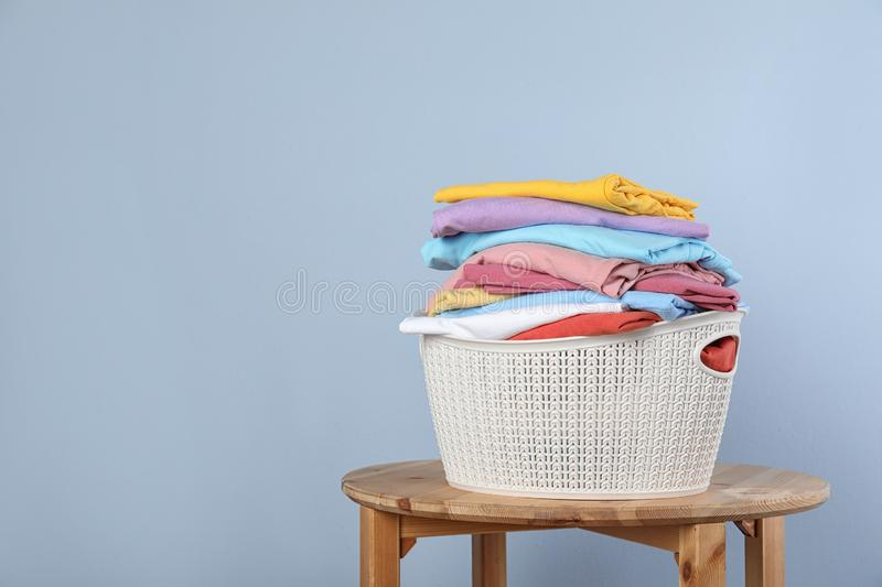 Plastic laundry basket with clean clothes on stool against color background. Space for text royalty free stock photos