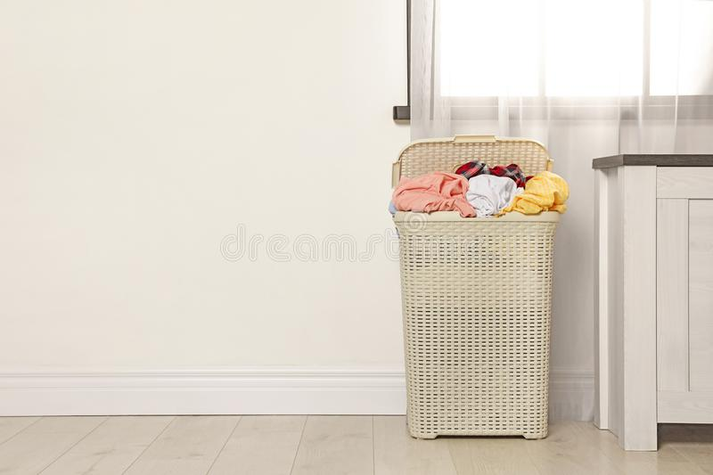 Plastic laundry basket full of dirty clothes on floor near light wall in room. Space for text stock image