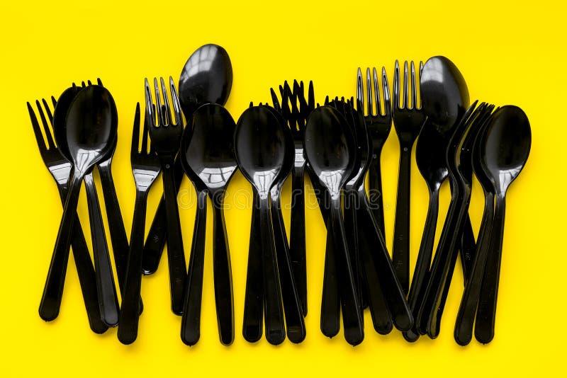 Plastic lepels en vorkengebruik en het concept van de Aardebescherming met tafelgereedschap op gele hoogste mening als achtergron royalty-vrije stock fotografie