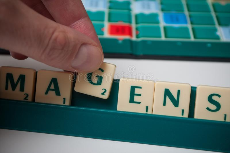 Plastic letters in hand on Scrabble board game stock photo