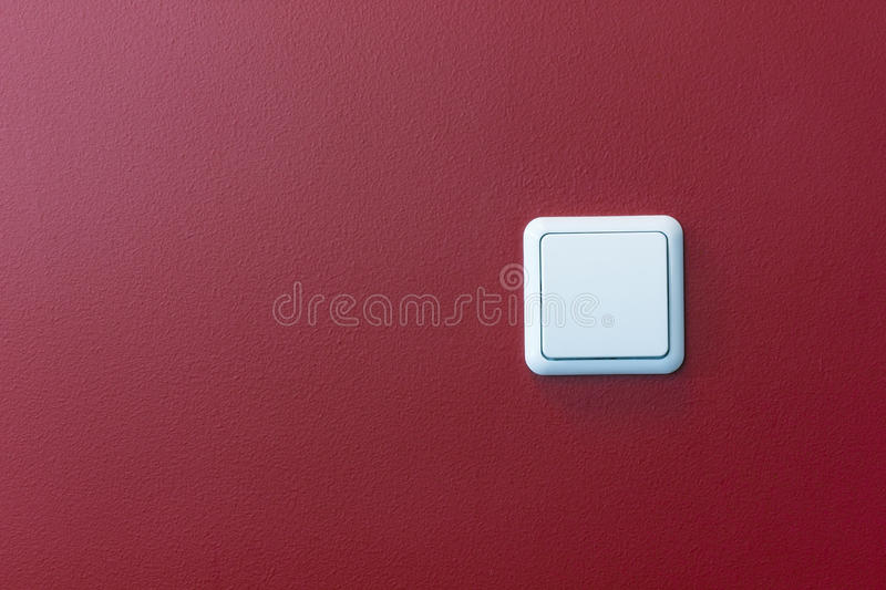 Plastic light switch in the red wall stock photography