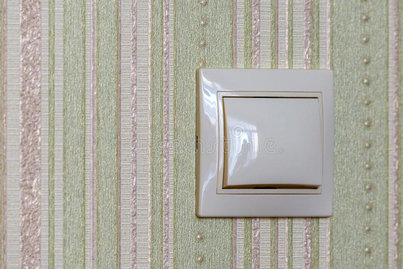 Plastic light switch, turn on or turn off the lights. Wallpaper, button, interior, power, background, control, electricity, energy, household, objects, home stock image