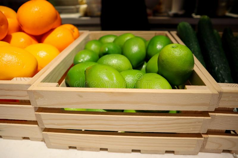 Plastic limes in the wooden basket royalty free stock photo