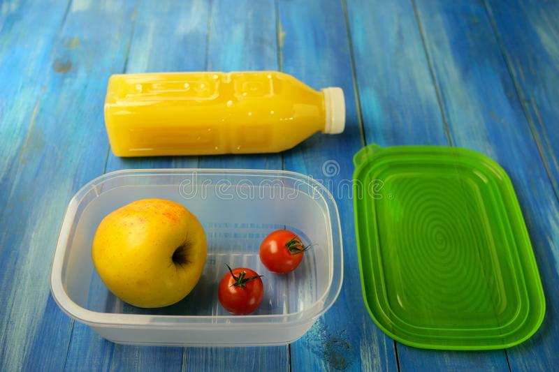 Plastic lunch box with large ripe apple and two cherry tomatoes on blue wooden table. Nearby is plastic bottle of orange juice and royalty free stock images