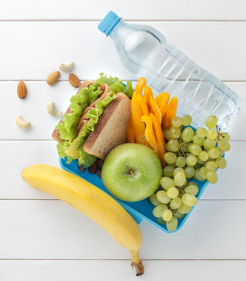Plastic lunch box with sandwich, fruits, vegetables, nuts and water on white wooden table. royalty free stock photo
