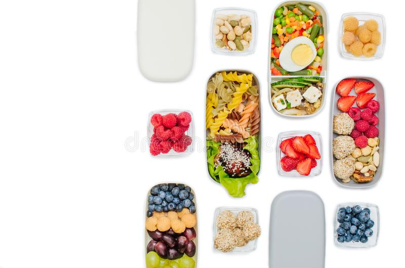Plastic lunch boxes filled with healthy food isolated on white background stock photography