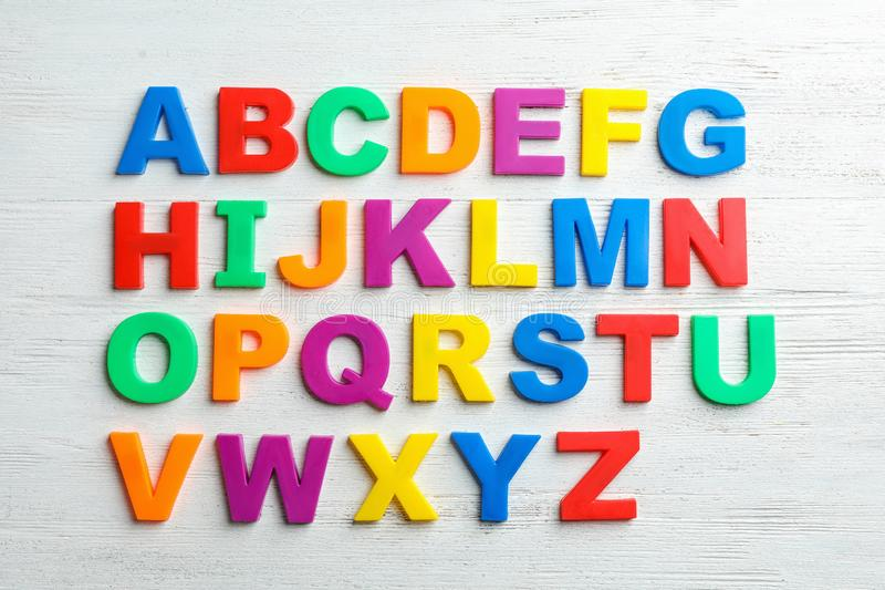 Plastic magnetic letters on wooden background, top view. Alphabetical order stock photos
