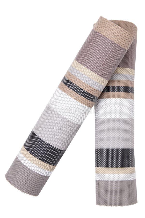 Plastic mattenachtergronden Twee geweven plastic matten met een kleurrijk gestreept die patroon op een witte achtergrond wordt ge stock foto