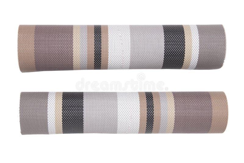 Plastic mattenachtergronden Twee rollen van geweven kunststof met een kleurrijk die patroon op een witte achtergrond wordt geïsol royalty-vrije stock foto