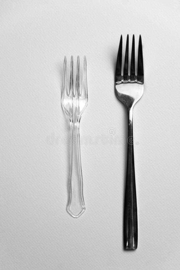 Plastic and metal silver fork for food or environmental recycle on white background stock photography