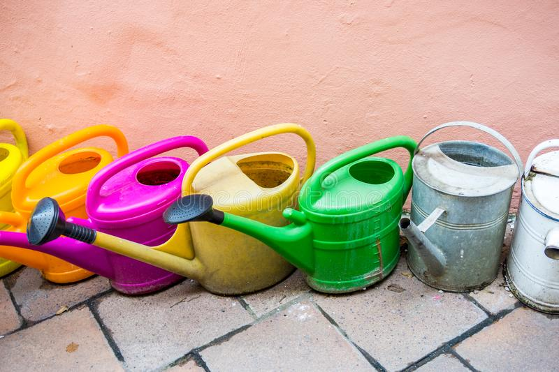 Plastic and metal watering cans and pots for watering plants various colors. Old and used plastic and metal watering cans and pots in various colors for watering stock photography