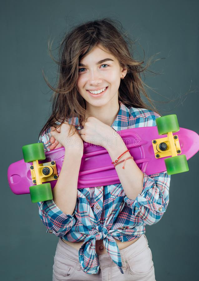 Plastic mini cruiser board. Spring. Urban scene, city life. ready to ride on the street. Hipster girl with penny board. Skateboard sport hobby. Summer activity stock photography