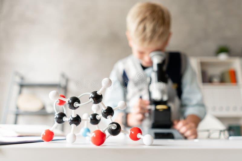 Plastic model van atomen en molecules in de voorgrond Een jonge jongen in een witte overhemd en een sweater onderzoekt de steekpr royalty-vrije stock foto
