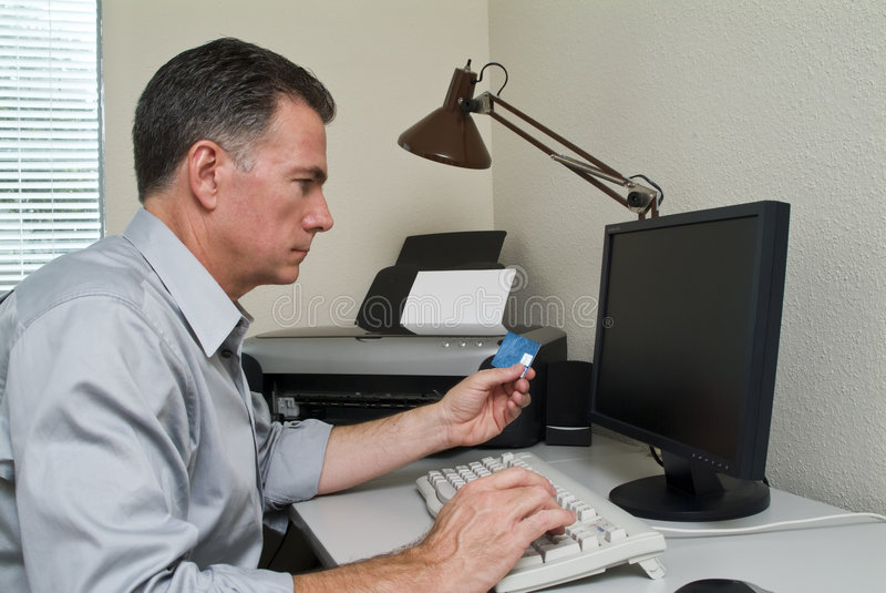 Plastic Money. A man sitting at a computer with a credit card in his hand as if making a purchase royalty free stock photo