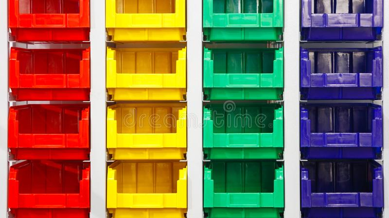 Plastic multicolored box containers on the modern warehouse for piece small storage of goods.  royalty free stock images
