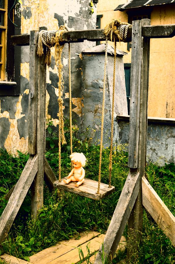 Plastic naked doll on a wooden swing. royalty free stock images