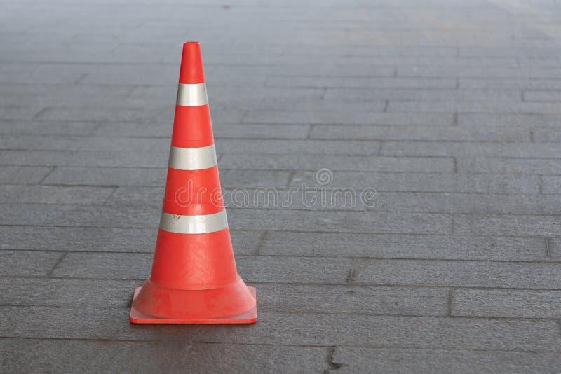 Plastic orange traffic cone on city street. Description: Plastic orange traffic cone on city street, alert, attention, barrier, boundary, caution, danger stock image