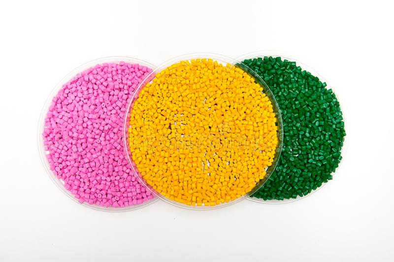 Plastic pellets . Colorant for polymers in granules. Worker wearing gloves takes plastic pellets with tweezers.  stock photography