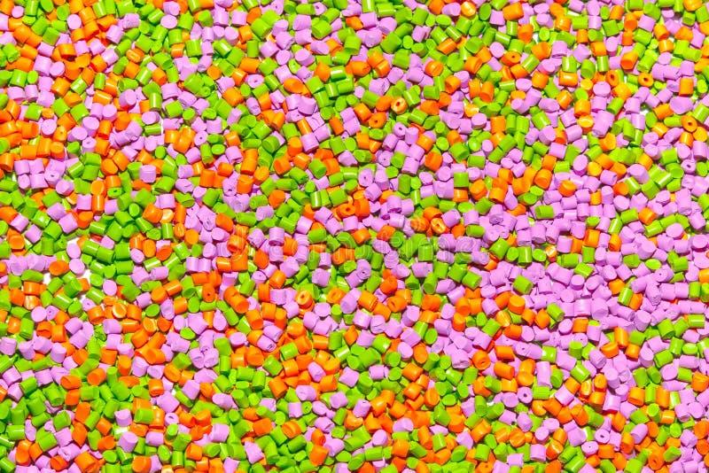 Plastic pellets. Orange green and pink Polypropylene granules sc royalty free stock photos