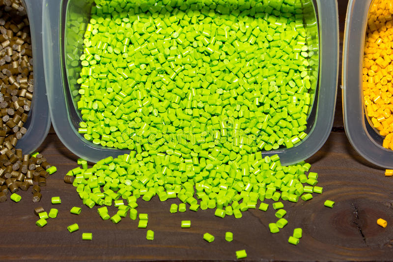 Plastic pellets are poured from a measuring container on laboratory table royalty free stock image