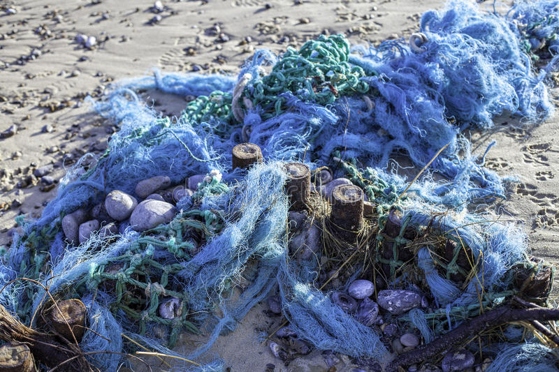 Plastic pollution - blue tangled fishing nets washed up on the b royalty free stock images