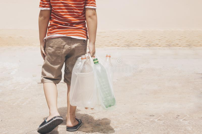 Plastic pollution on land. Little boy collecting plastic bottles. Kid carry garbage bag. Free space royalty free stock photography